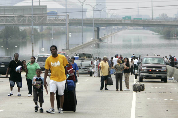 Residents of New Orleans rescued by police boats walk from floodwaters in front of the Superdome in New Orleans September 1, 2005. New Orleans Mayor Ray Nagin issues an urgent plea for relief, saying the flooded city lacks food for thousands of Hurricane Katrina's refugees as well as buses to evacuate them. REUTERS/Jason Reed JIR/mk FOR BEST QUALITY IMAGE: ALSO SEE GF2E54L176S01 - RTRM9IH