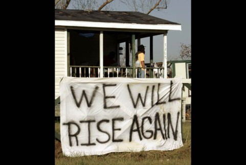 "Survivors of Hurricane Katrina clean out their house after hanging a sign out front reading ""We Will Rise Again"" in Clermont Harbor, Mississippi September 7, 2005. Police threatened to force reluctant Hurricane Katrina survivors to leave a ruined and fetid New Orleans on Wednesday as a political storm grew over the botched response to the disaster that some say could cost $150 billion. REUTERS/Brian Snyder"